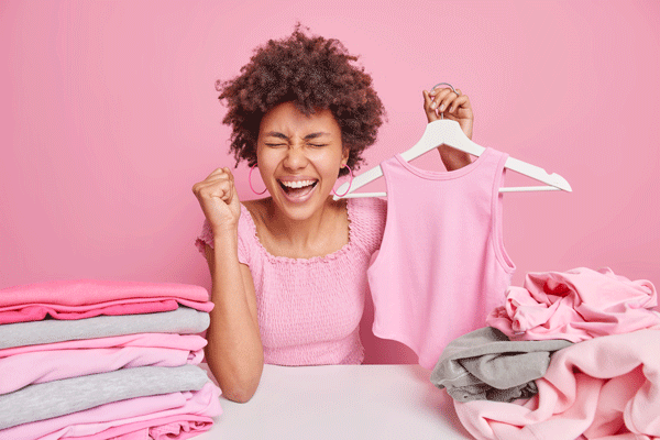 overjoyed-dark-skinned-woman-with-curly-hair-cleches-fist-from-happiness-holds-apparel-hanger-sits-table-folds-laundry-isolated-pink-wall